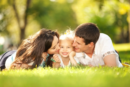 Photo for Happy mother and father kissing their daughter in the park - Royalty Free Image