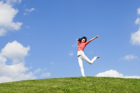 Photo for pretty young woman jumping on green grass - Royalty Free Image