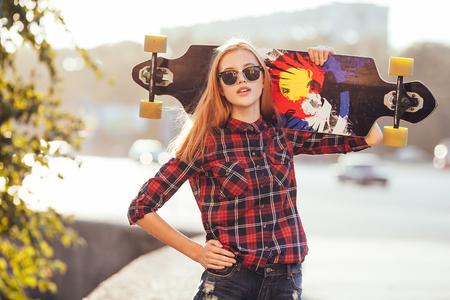 Foto de Sport fashion girl posing in summer with skateboard - Imagen libre de derechos