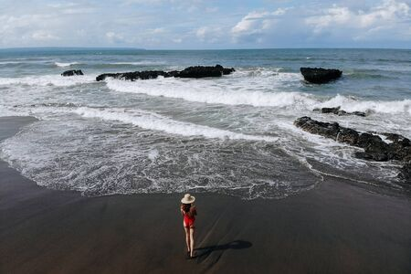 Foto de Aerial view of woman enjoy ocean with big waves and rocks, beach with black sand in red bikini and straw hat walking. Vacation in Bali. Photo from drone - Imagen libre de derechos