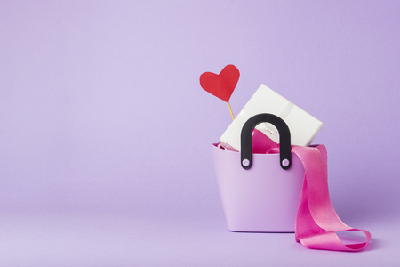 Photo pour Small plastic bag for shopping, gift boxes, heart on a stick, pink ribbon, violet background. Concept of pre-holiday shopping, sale, Black Friday, Cyber Monday, Valentine's Day. - image libre de droit