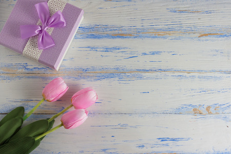 Photo pour Pink Tulips and Gift Box on a White Wooden Background. Copy space. Flat lay, top view. - image libre de droit