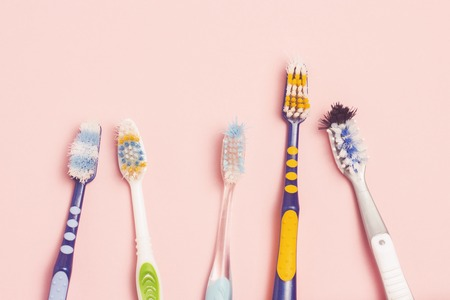 Photo for Several different used toothbrushes on a pink background. Toothbrush change concept, oral hygiene, big and friendly family, toothbrush selection. Flat lay, top view - Royalty Free Image