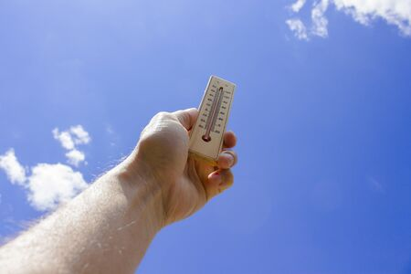 Foto de The male hand holds a thermometer against the blue sky. The concept of heat, global warming. - Imagen libre de derechos