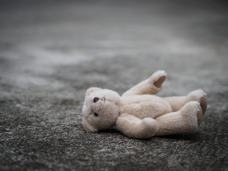 Photo pour Teddy bear is laying down on the floor. lonely concept. international missing children's day. - image libre de droit