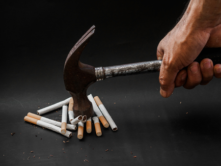 Foto de Hammer hitting and destroy cigarettes on black background. Quitting smoking concept. world no tobacco day - Imagen libre de derechos