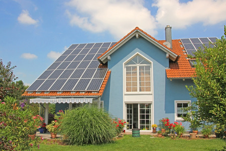 Photo pour modern new built house and garden, rooftop with solar cells, blue front with lattice window  - image libre de droit