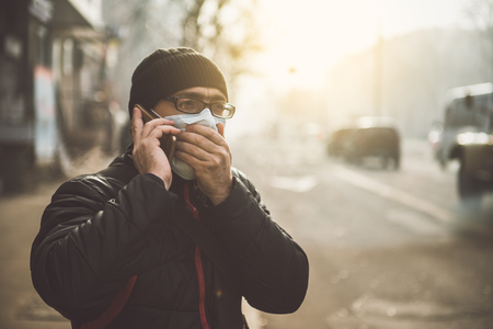 Foto de A man wearing a mask on the street. Protection against virus and grip - Imagen libre de derechos