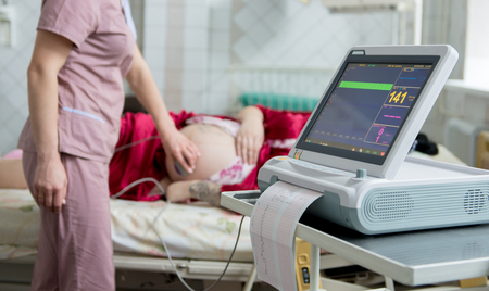 Photo pour Pregnant woman with electrocardiograph check up for her baby. Fetal heart monitoring. Diagnostic, healthcare, medical service - image libre de droit