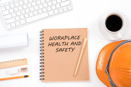 Foto de Workplace health and safety concept. Top viwe of modern workplace with safety helmet, office supplies, a cup of coffee and keyboard on white background. - Imagen libre de derechos