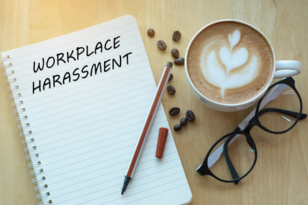 Photo for Workplace harassment concept on notebook with glasses, pencil and coffee cup on wooden table. Business concept. - Royalty Free Image