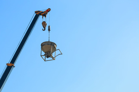 Foto de machinery crane hoisting cement mortar mixer bucket container in construction site building industry - Imagen libre de derechos