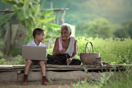 Foto de A boy and grandmother with a laptop at cottage - Imagen libre de derechos