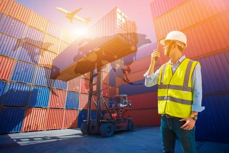 Foto de Foreman control loading containers box from cargo freight ship for import export - Imagen libre de derechos