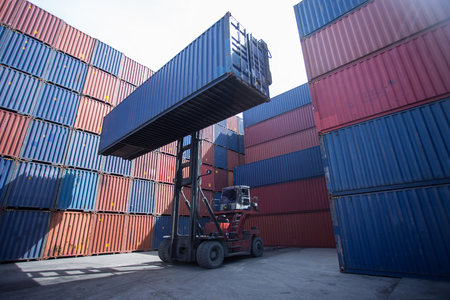 Forklift truck lifting cargo container in shipping yard or dock yard against sunrise sky for transportation import