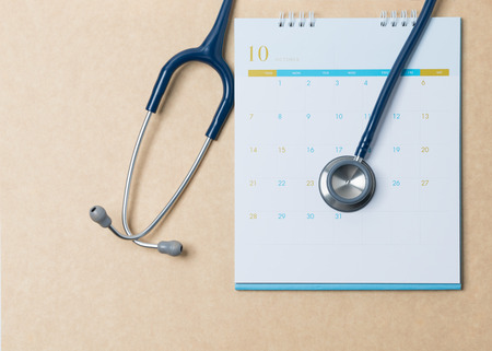 Photo pour Stethoscope and a calendar. Doctor's appointment and service in the hospital. - image libre de droit