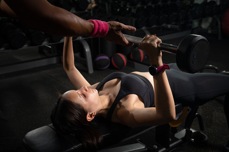 Foto de Personal trainer helping woman bench press in gym, Training with barbell - Imagen libre de derechos