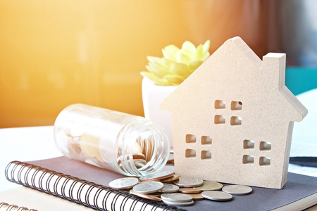 Business, finance, savings, property ladder, mortgage or loan concept : Wood house model and coins scattered from glass jar on notebook paper