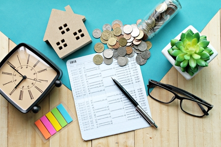 Photo pour Business, finance, saving money, property loan or mortgage concept :  Top view or flat lay of wood house model, saving account book or financial statement and coins on office desk table - image libre de droit