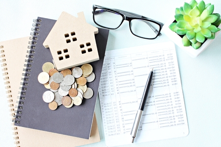 Foto de Business, finance, saving money, property loan or mortgage concept :  Top view or flat lay of wood house model, saving account book or financial statement and coins on office desk table - Imagen libre de derechos