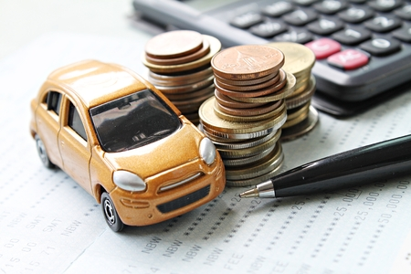 Foto de Business, finance, saving money or car loan concept : Miniature car model, coins stack, calculator and saving account book or financial statement on desk table - Imagen libre de derechos