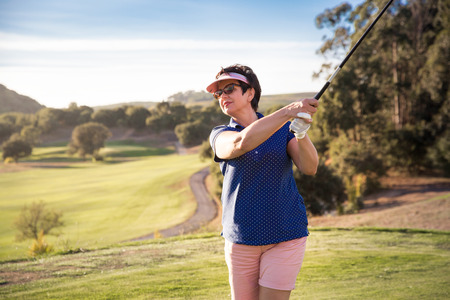 Photo for Mature woman playing golf. Golfer hitting golf shot with driver club on course. Beautiful sunny Landscape, green hills, blue sky. Portugal. - Royalty Free Image