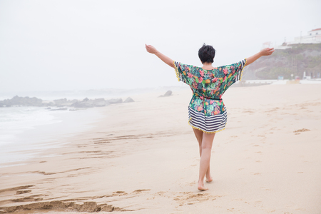 Foto de Portrait of a Happy mature woman with outspread arms Enjoying freedom on the Ocean Beach. Freedom of Travel Vacation. Wellness and Happiness Lifestyle Concept. Portugal. Santa Cruz - Imagen libre de derechos