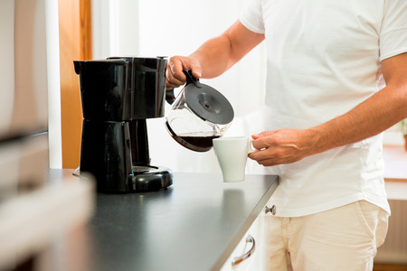 Foto de Man in the kitchen pouring a mug of hot filtered coffee from a glass pot. Having breakfast in the morning - Imagen libre de derechos