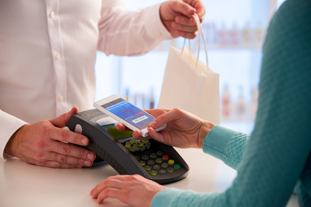 Foto de Wireless payment using smartphone and NFC technology. Close up. Customer paying with smart phone in pharmacy. Close Up shopping - Imagen libre de derechos