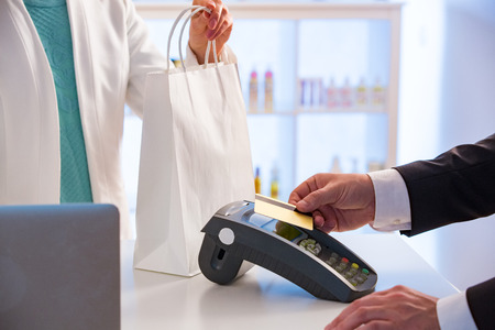 Photo pour Customer paying with contactless card. NFC technology payment in store. Close Up. Shopping in pharmacy. - image libre de droit