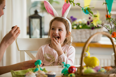 Photo for Mother and daughter celebrating Easter, eating chocolate eggs. Happy family holiday. Cute little girl in bunny ears laughing, smiling and having fun. - Royalty Free Image