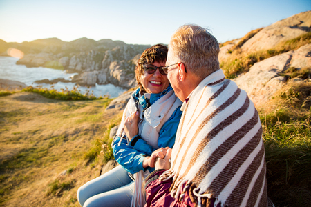 Photo for Loving mature couple hiking, sitting on windy top of rock, exploring. Active Mature man and woman wrapped in blanket, hugging and Happily smiling. Scenic view of sea, mountains. Norway, Lindesnes. - Royalty Free Image