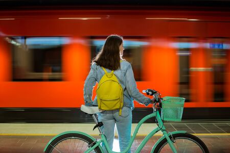 Photo for Teenager girl in jeans with yellow backpack and bike standing on metro station, waiting for train, smiling, laughing. Orange train passing by behind the girl. Futuristic subway station. Finland, Espoo - Royalty Free Image