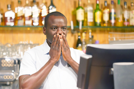 Photo for Male bartender made a mistake in the bill, emotion. A barmaid registrating new order by cash register. A restaurant worker registrating new order by cash register. The concept of service. - Royalty Free Image