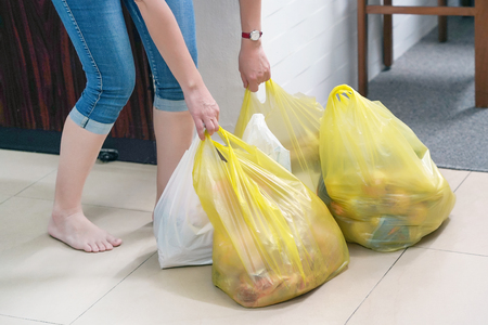 Foto de Woman with food plastic bags at home. Housewife with food packages after a supermarket in the hallway of her apartment. - Imagen libre de derechos