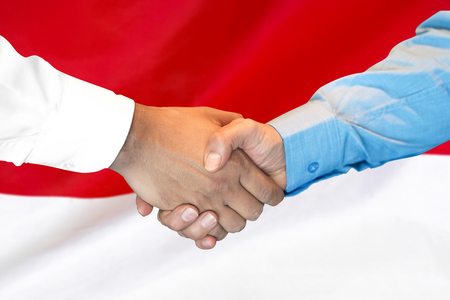Photo for Business handshake on Monaco flag background. Men shaking hands and Monaco flag on background. Support concept - Royalty Free Image