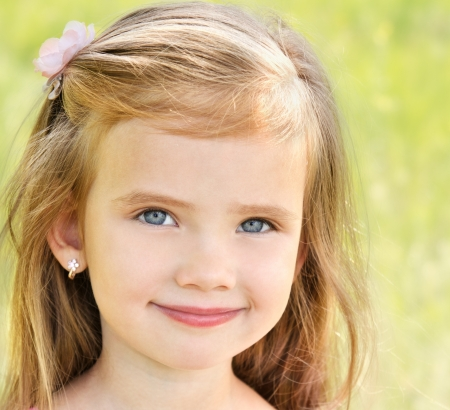 Outdoor portrait of adorable smiling little girl in summer day