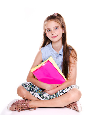 Photo pour Portrait of cute smiling happy little school girl child teenager sitting on a floor and holding the books isolated on a white - image libre de droit
