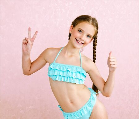 Photo pour Portrait of cute smiling little girl child schoolgirl teenager in swimsuit and finger up isolated fashion concept - image libre de droit