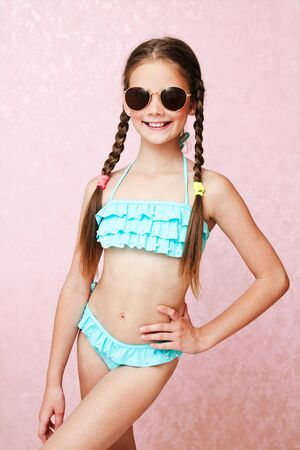 Foto de Portrait of cute smiling little girl child schoolgirl teenager in swimsuit and sunglasses isolated fashion concept - Imagen libre de derechos