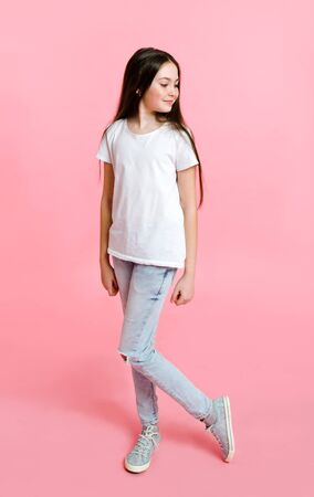 Portrait of adorable smiling little girl child in the white t-shirt isolated on a pink