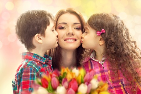 Portrait of children kissing her mother with flowers  Mother s day concept  Family holiday