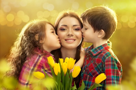 Photo for Portrait of children kissing her mother with flowers  Spring, March 8, International Womens, Mothers day, family holiday - Royalty Free Image