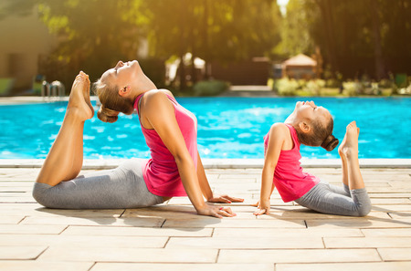Photo pour Mother and daughter doing exercise outdoors. Healthy lifestyle. Yoga - image libre de droit
