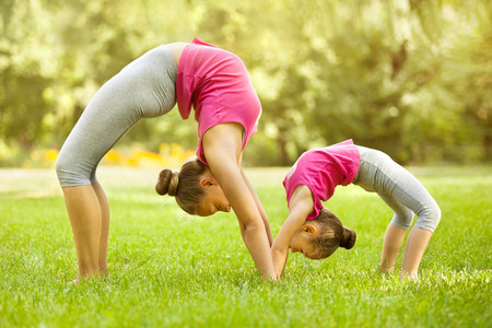 Photo for Mother and daughter doing exercise outdoors. Healthy lifestyle. Yoga - Royalty Free Image