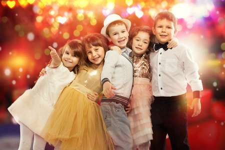 Group of happy kids in celebratory clothes with colorful lights on background. Holidays, christmas, new year, x-mas concept.