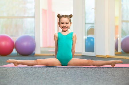 Photo for Little girl gymnast sitting in the cross split in gym. Sport, active lifestyle concept - Royalty Free Image