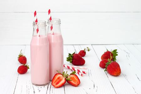 Foto de Strawberry milk in traditional glass bottles with straws on old vintage wooden background - Imagen libre de derechos
