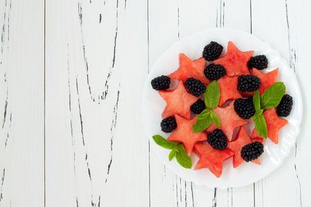 Foto de Refreshing watermelon salad with blackberries and mint. Fresh star shaped watermelon. Copy space background - Imagen libre de derechos