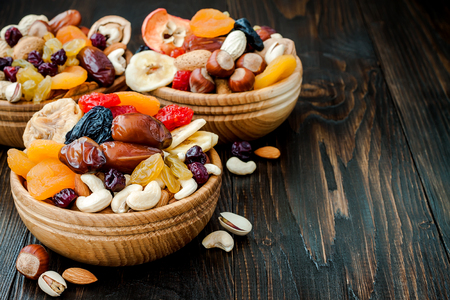 Photo for Mix of dried fruits and nuts on dark wood background with copy space. Symbols of judaic holiday Tu Bishvat - Royalty Free Image